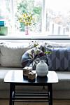 SKAP ZEN: Dagslyset strømmer inn fra de høye vinduene i stuen. Sofaen er en eldre modell fra Bolia og avisbordet er gjenbruksfunn som har fått en omgang med sort maling. Foto: Pernille Kaalund